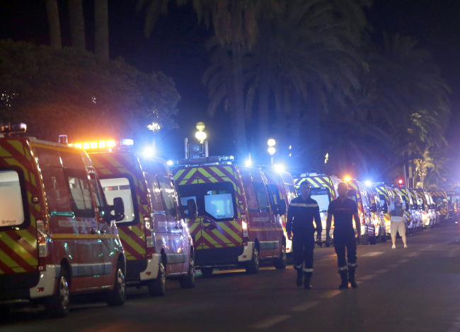 "Ambulances line up near the scene of an attack after a truck drove on to the sidewalk and plowed through a crowd of revelers who'd gathered to watch the fireworks in the French resort city of Nice, southern France, Friday, July 15, 2016. A spokesman for France's Interior Ministry says there are likely to be ""several dozen dead"" after a truck drove into a crowd of revelers celebrating Bastille Day in the French city of Nice. (AP Photo/Claude Paris)"